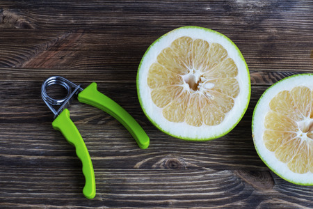 The concept of a healthy lifestyle. Pamela fruits and hand espander. Stock Photo