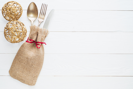 grunge flatware: Rustic cutlery set: vintage knife, fork and spoon on a white wooden background. Table with antique cutlery on the burlap with copy space, top view, flat lay. Cutlery wrapped in burlap.