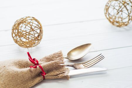 grunge cutlery: Rustic cutlery set: vintage knife, fork and spoon on a white wooden background. Table with antique cutlery on the burlap with copy space, close-up. Cutlery wrapped in burlap.