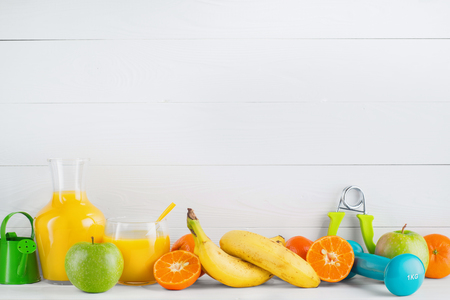 hand gripper: Fruit and juice, orange, tangerine, apple, banana, dumbbell, hand gripper on white wooden background with copy space.  Healthy lifestyle and diet concept. Healthy eating for weight loss.
