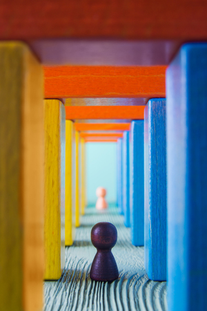 Abstract man into the colorful wooden corridor. Concept of success. Abstract man in a multicolored wooden tunnel. Two persons walk to the light in the end of the tunnel. Stock Photo
