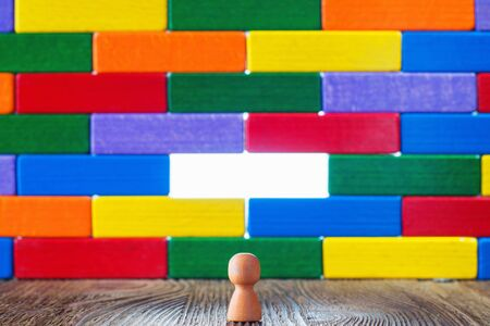 afflatus: Abstract man standing in front of a wall or barrier of multicolored wooden blocks, through which the light shines. Success concept. Business metaphor.