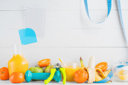 hand gripper: Fruit and juice, orange, tangerine, apple, banana, dumbbell, hand gripper and a blank sheet on white wooden background with copy space. Healthy lifestyle, diet concept. Healthy eating for weight loss.