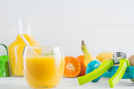 hand gripper: A glass of fresh orange juice and fruits, tangerine, apple, banana, dumbbell, hand gripper on white wooden background. Healthy lifestyle and diet concept. Healthy eating for weight loss.