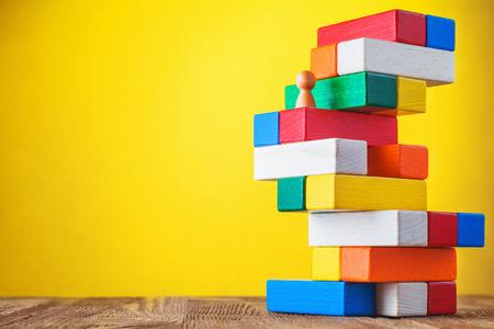 黄色の背景にカラフルなキャリアの階段を登る実業家のビジネスの比喩。ウッド ブロックの階段を使用しての概念を行きます。成功を達成します。
