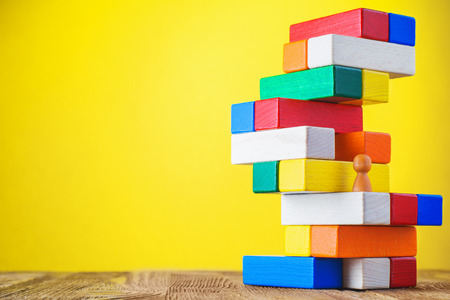 Business metaphor of businessman climbing colorful career stairs on yellow background. Going up concept using stairway of wood blocks. Achieving success. Business competition. Career, social status. Stock Photo