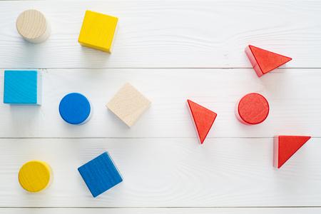 흰색 배경, 상위 뷰, 평면 누워 다채로운 나무 블록. 어린이 창의력 장난감. 기하학적 모양 - 큐브, 삼각형 프리즘, 실린더. 논리적 사고의 개념. 스톡 콘텐츠