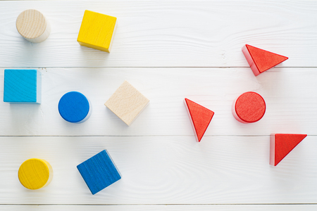 Colorful wooden blocks on white background, top view, flat lay. Children's creativity toys. Geometric shapes - cube, triangular prism, cylinder. The concept of logical thinking.
