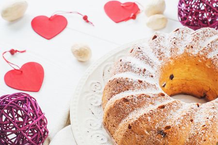 napkin ring: Bundt cake with raisins and sugar powder on a white plate. Ring cake with icing sugar on white wooden table. Festive treat. Festive table setting for Valentines Day