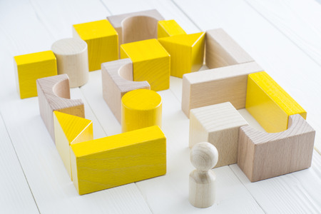 complicated journey: The yellow-beige maze of wooden blocks of various shapes. Man standing in front of the maze. Difficult path to find exit, business concept. The concept of a strategy, search for solutions. Stock Photo