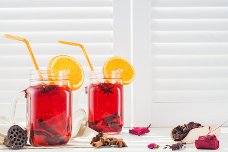 Two fruit tea in vintage glass jars with drinking straw against vintage white wooden shutters background. Vintage mason jars with ice red tea, cinnamon and star anise on white window sill.