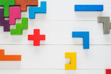 Concept of creative, logical thinking. Different colorful shapes wooden blocks on white wooden background, flat lay, copy space. Geometric shapes in different colors, top view. Abstract Background. Standard-Bild