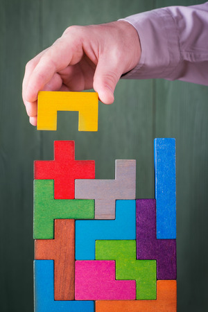 Hand with wooden toy blocks. Businessman builds a tower of wooden multi-colored blocks.  Concept of business success, cooperation, achievement.