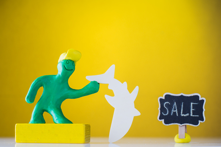 Plasticine man holds a fish. Wooden tablet with an inscription - sale.  Stock Photo