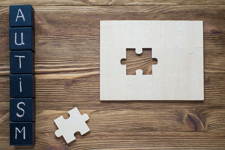 asperger: Puzzle pieces and black wooden cubes with word AUTISM on wooden background, top view, flat lay. Autism Spectrum Disorder (ASD).  Autism awareness. Concept of autism word.  Stock Photo