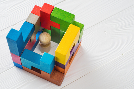 trapped: Business metaphor, businessman in a trap on white wooden background with copy space. Businessman trapped inside a abstract room from colourful wooden blocks. The concept of problems in business.