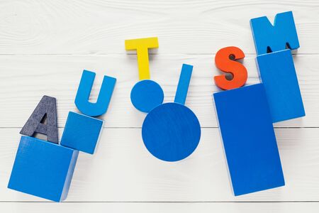 developmental disorder: Word Autism built of colorful wooden blocks on a white wooden background with copy space, top view. Concept of autism word, flat lay. Autism Spectrum Disorder (ASD). Stock Photo