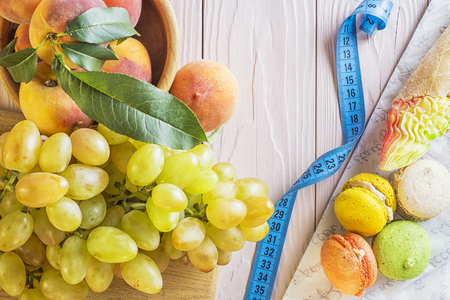 unhealthy thoughts: Choosing between Fruits and Sweets. Healthy versus unhealthy food. Weight Loss. Unhealthy tempting cakes and healthy fruits. Healthy and unhealthy food is divided by a measuring tape.