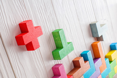 Concept of creative, logical thinking. Different colorful shapes wooden blocks on white wooden background, copy space. Geometric shapes in different colors. Abstract Background. Stock Photo