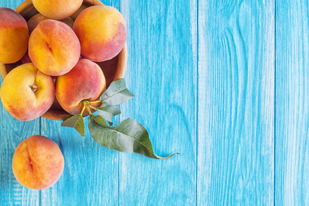 Fresh ripe peaches in a wooden bowl on a blue wooden background. Fresh fruits background.