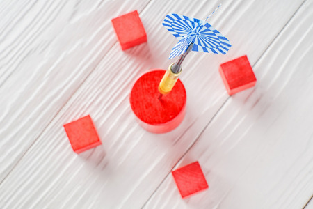 Dart stuck into wooden target. Concept of achieving your goal. Metaphor to target marketing or target concept. Stock Photo