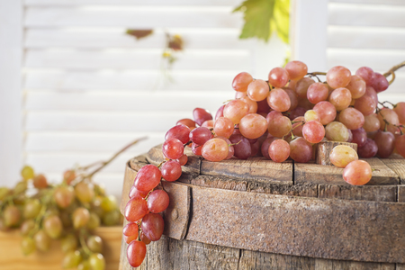Still life of red grapes on a wooden barrel. Concept of the grape harvest, wine making and viticulture. Reklamní fotografie
