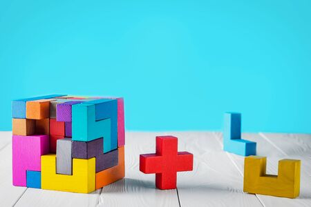 reason: Concept of decision making process. Concept of creative, logical thinking. Different geometric shapes wooden blocks on white wooden background, copy space. Geometric shapes in different colors.