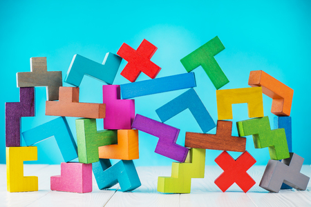 Abstract geometric design. Multicolored shapes wooden blocks on blue background. Geometric shapes in different colors. Concept of creative, logical thinking or problem solving.