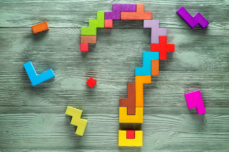 Question mark made of colorful wooden blocks on green wooden background, top view. Concept of creative, logical thinking. Stock Photo