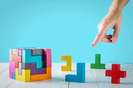 Konzept des Entscheidungsprozesses, logisches Denken. Logische Aufgaben Rätsel, finde das fehlende Stück des vorgeschlagenen. Hand, die hölzernes Puzzlespielelement anhält. Die Hand zeigt die richtige Entscheidung an.