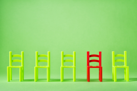 Unique red chair in row of green others. Leadership concept. Empty chairs by wall. The concept of uniqueness, distinction from others. Stock Photo
