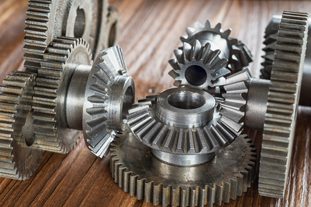 Steel gear and reducer, engineering details on wooden background. Metal cogwheels. Industry Concept.