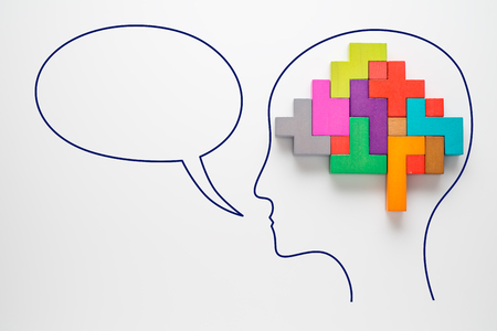 Head with colourful shapes of abstract brain with speech bubble. Human brain is made of multi-colored wooden blocks. Creative business concept.