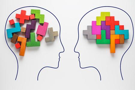 O conceito de pensamento racional e irracional de duas pessoas. Cabeças de dois povos com formas coloridas do cérebro abstrato para o conceito da ideia e dos trabalhos de equipa. Duas pessoas com diferentes pensamentos. Foto de archivo