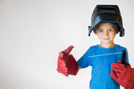 Happy little kid in welder mask and welding equipment. Welding equipment, welding mask, protective leather gloves, welding electrodes. Fun concept. Child dreaming of future profession. Career choice.