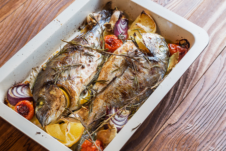 Two delicious whole baked fish. Baked dorado with lemon, onions, rosemary, cherry tomatoes, and spices on a wooden background. Delicious roasted dorado on oven tray. Diet and healthy food. Top view.