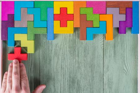 Concept de processus de prise de décision, pensée logique. Tâches logiques Conundrum, trouvez la pièce manquante du projet. Main tenant l'élément de puzzle. Fond avec des blocs de bois de formes colorées