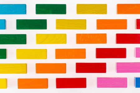 Mehrfarbiger hölzerner Hintergrund. Hintergrund mit hölzernen Blöcken der bunten Formen. Bunte Wand, Spielzeug farbige hölzerne Ziegelsteine. Multicolor Holzblöcke.