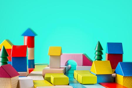 Hölzernes Haus des Spielzeugs von farbigen Blöcken auf blauem Hintergrund. Gebäude, Baukonzept. Immobilien, ein Haus von einem hölzernen Würfel, auf Schreibtisch konstruierend.