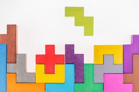 Hölzerne Blöcke der verschiedenen bunten Formen auf beige Hintergrund, flache Lage. Geometrische Formen in verschiedenen Farben, Draufsicht. Konzept des kreativen, logischen Denkens oder des Lösens von Problemen. Kopieren Sie Platz. Standard-Bild