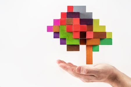 Menschliche Hand, die abstraktes Gehirn hält. Das menschliche Gehirn besteht aus mehrfarbigen Holzklötzen. Standard-Bild