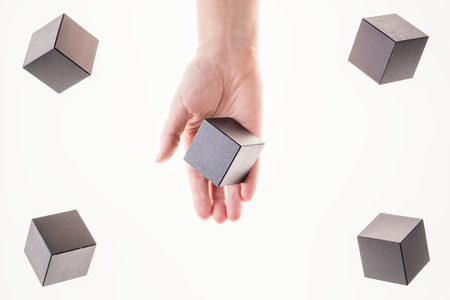 Black wooden cubes are floating. A womans hand takes a floating cube.  Concept of creative, logical thinking. Abstract background with cubes with copy space. Floating shapes. Standard-Bild
