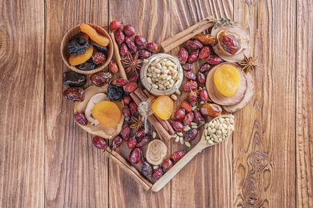 Mischung von Nüssen, von Trockenfrüchten, von getrockneten Hagebutten und von Gewürzen in Form eines Herzens auf einem rustikalen hölzernen Hintergrund. Konzept des gesunden Snacks. Verschiedene Nüsse und Trockenfrüchte mit Kopienraum.
