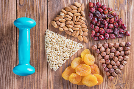 Dried apricots and nuts on a wooden table, round composition. Circle divided into parts made of a nuts and dried apricots. Concept of healthy snack. Various nuts and dried fruits and dumbbell.