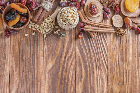 Mix of nuts, dried fruits, dried rose hips, and spices on a rustic wooden background. Concept of healthy snack. Various nuts and dried fruits. Standard-Bild