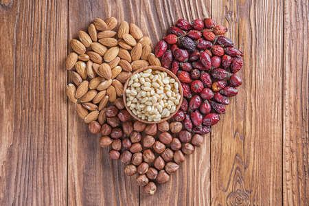 Heart of nuts and dried rose hips on wooden background. Almonds, hazelnuts, pine nuts and dried hips.  The concept of a healthy lifestyle. Standard-Bild