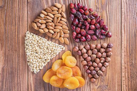 Getrocknete Aprikosen und Nüsse auf einem Holztisch, runde Zusammensetzung. Kreis in Teile aus Nüssen und getrockneten Aprikosen aufgeteilt. Konzept des gesunden Snacks. Verschiedene Nüsse und Trockenfrüchte mit Kopienraum.