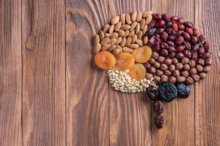 인간의 두뇌는 나무 테이블에 말린 된 살구와 견과류의 만들어집니다. 건강 식품의 개념입니다. 스톡 콘텐츠