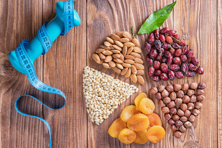 Dried apricots, nuts, measuring tape and dumbbell on a wooden table, round composition. Circle divided into parts made of a nuts and dried apricots. Concept of healthy lifestyle.  Standard-Bild