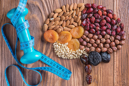 Human brain is made of dried apricots and nuts with measuring tape and dumbbell on a wooden table. Brain made of a nuts and dried apricots. Concept of healthy food and healthy lifestyle.